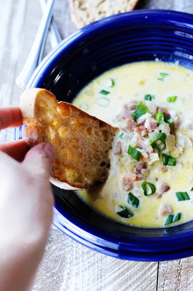 ham and cheese soup with scallion in blue bowl with hand dunking the bread in the soup