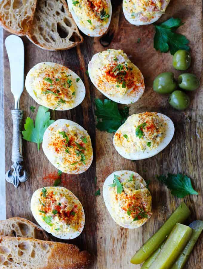 stuffed eggs on a board with bread, olives, pickles, bread on a side