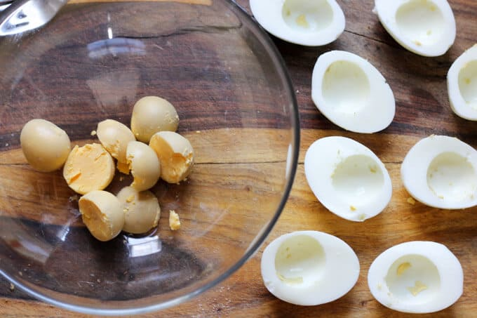 hard boiled eggs with egg yolks separated in a bowl and egg whites on a cutting board