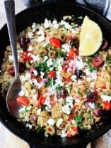 Cauliflower Fried Rice in a skillet with olives, feta, lemon and spoon