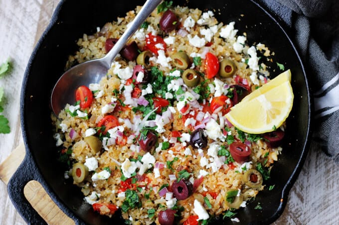 Fried riced cauliflower with Mediterranean twist in a skillet with spoon and lemon
