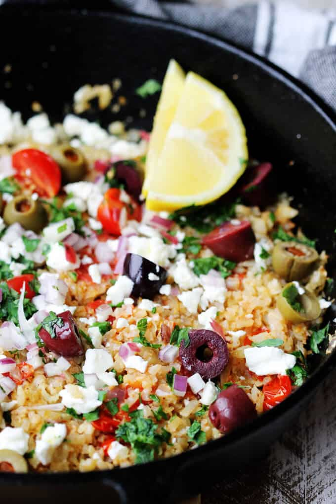 Cauliflower Fried Rice Mediterranean with feta, olives, tomatoes, lemon and parsley, close up shot