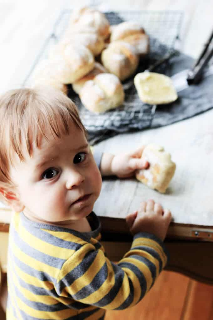 Child eating roll, with more rolls in the back