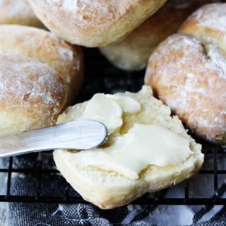 Breakfast rolls with one cut up and with spreader butter
