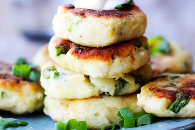 Potato cutlets stacked up on a plate with green onions around; horizontal shot