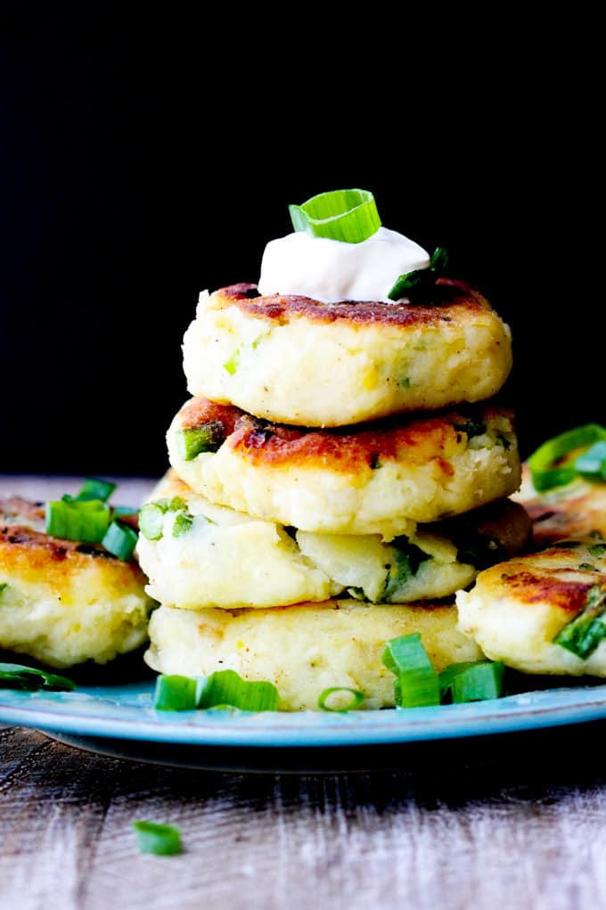Potato cutlets stack on a blue plate with black background