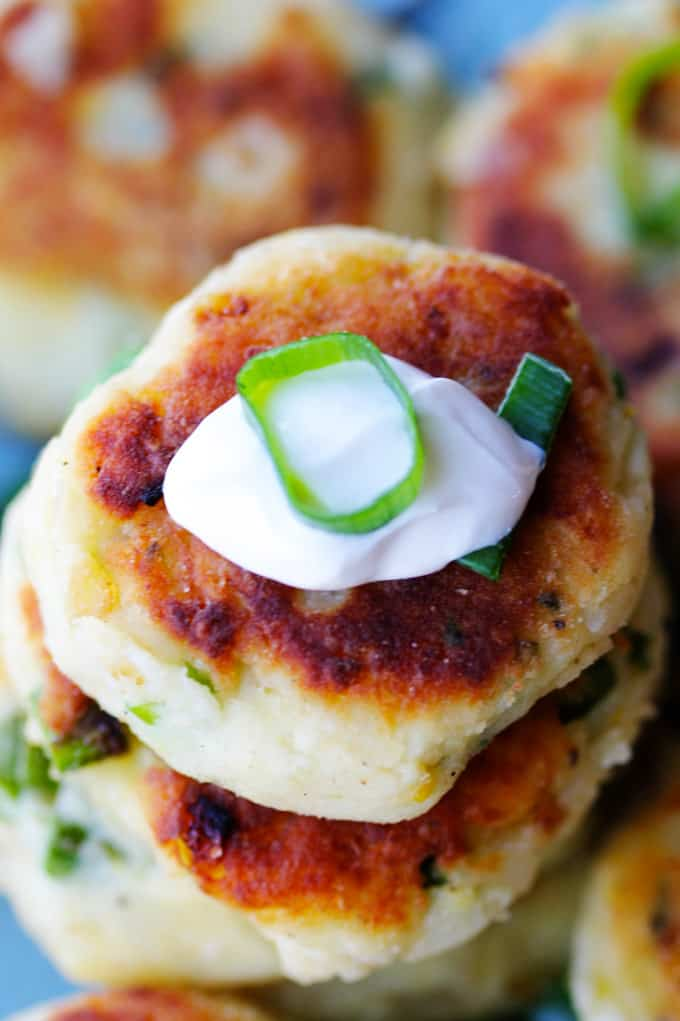Potato cutlets from the overhead with dollop of sour cream and scallion