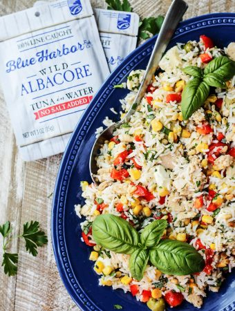 Italian Rice Salad with Tuna on a blue plate with tuna pouches on a side