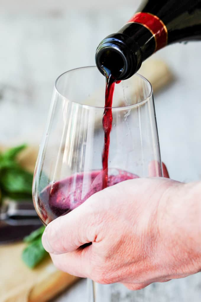Hand holding a wine glass with pouring red wine