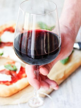 Glass of red wine with pizza in a background