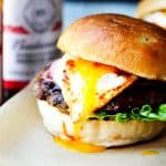 Smoky BBQ burger with runny egg yolk and sauces in the back