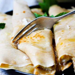 Fork cutting through crepe with apple sauce and ricotta with honey