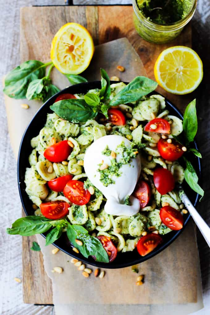 Black bowl of pesto pasta with tomatoes and Burrata cheese on top