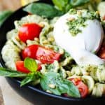 Burrata Cheese on top of pesto pasta with cherry tomatoes