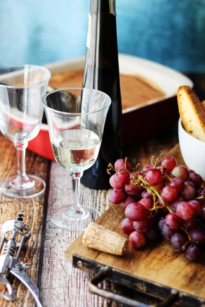 Italian Dessert Wine Moscato D'Asti in a glass with grapes and desserts on a side.
