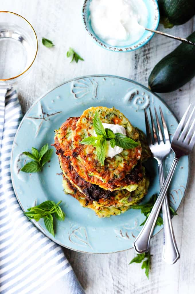 Overhead photo of Greek zucchini fritters on a blue plate with yogurt on a side and a glass of water