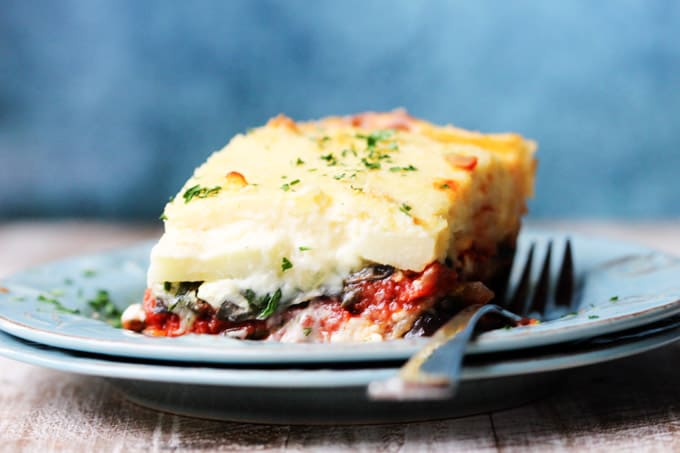 Horizontal shot of a vegetarian moussaka on a blue plate with fork