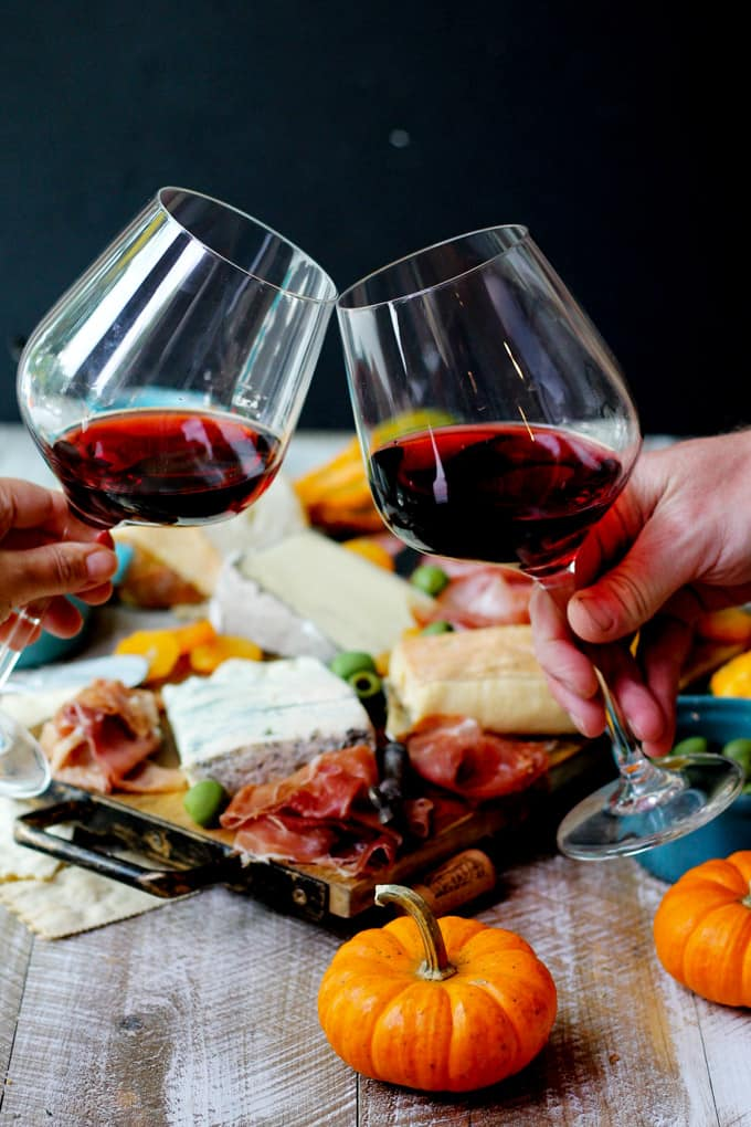 Glasses of red Italian wine and cheese with meat board