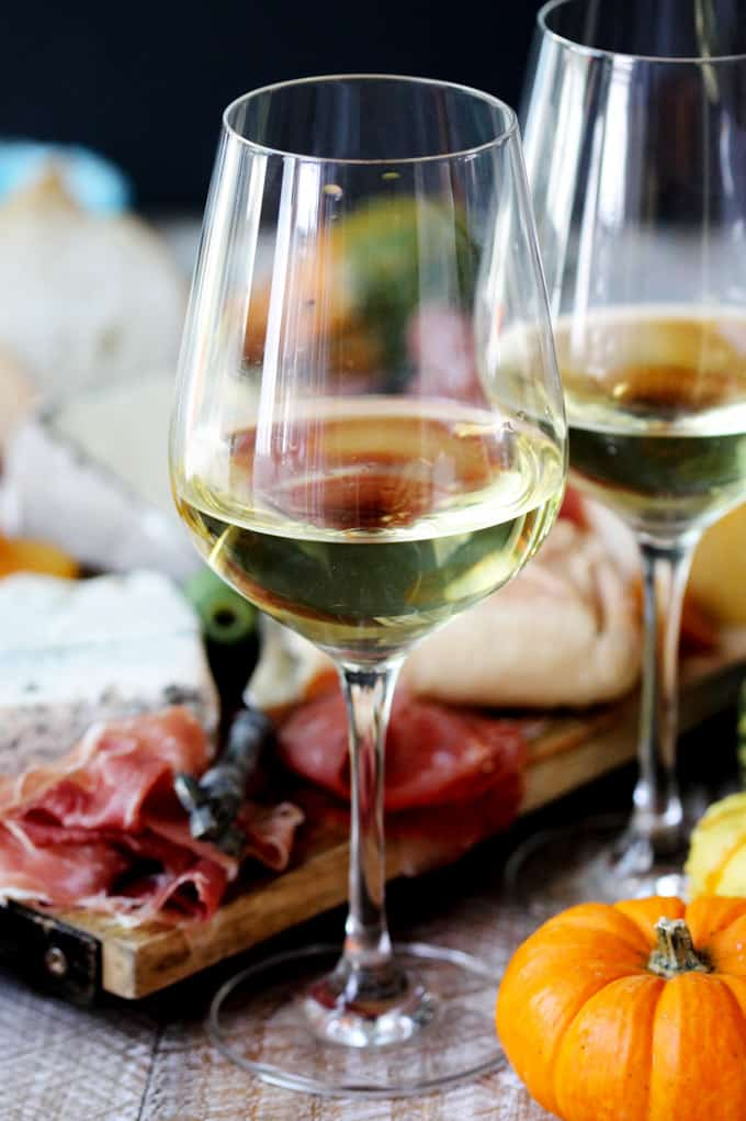 Two glasses with Italian white wine and meat with cheese board