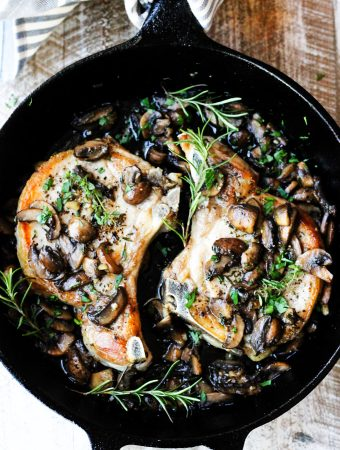 Mushroom pork chops with garlic butter and herbs in a skillet
