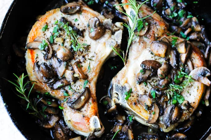 pork chops in cast iron skillet with mushrooms