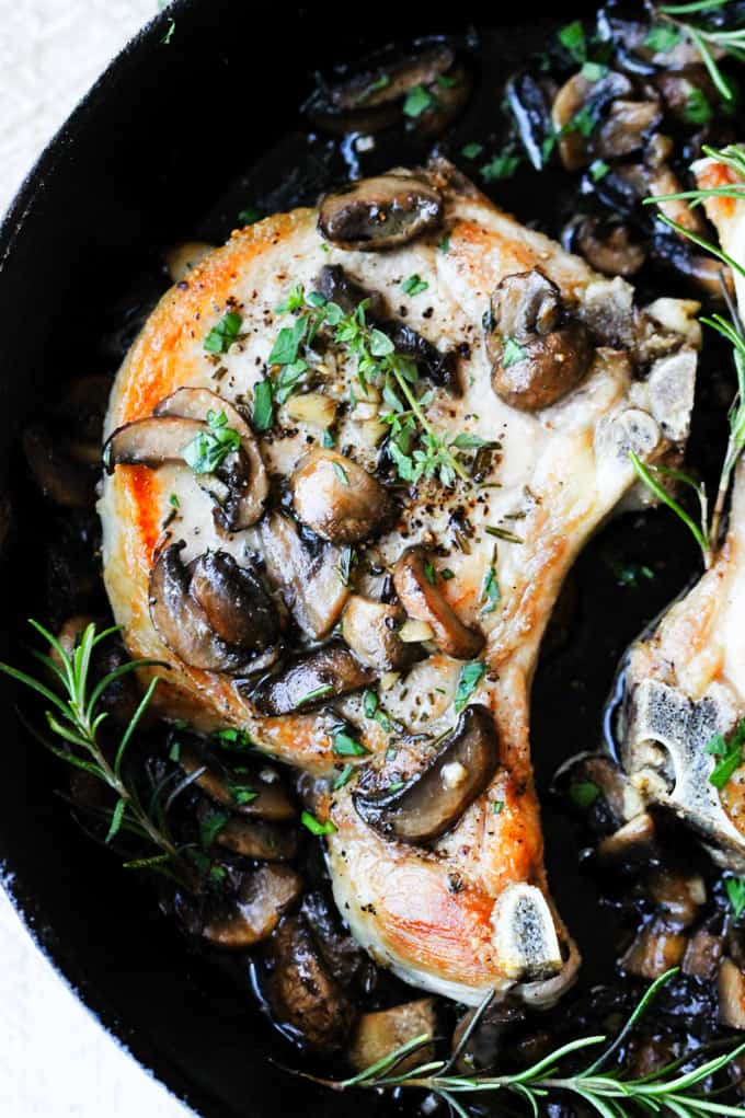 Pork chops with garlic butter mushrooms in a skillet