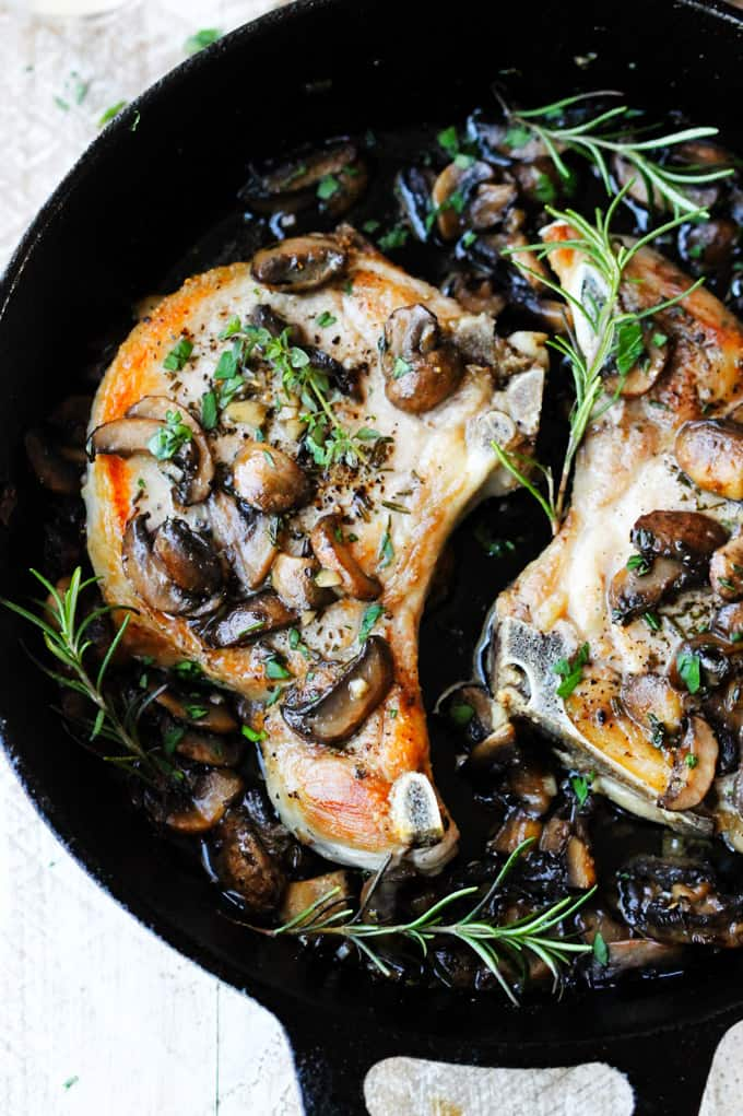 bone-in pork chops in a skillet with mushrooms