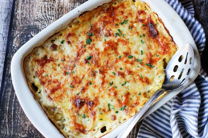 Acorn Butternut Squash Gratin in a casserole dish with spoon