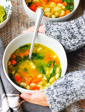 Serving Instant Pot Bean Soup with Spinach and Pesto in a bowl with a spoon