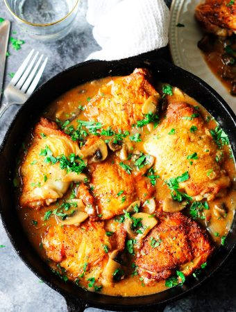 Chicken Chasseur in a skillet with fork on a side and water behind