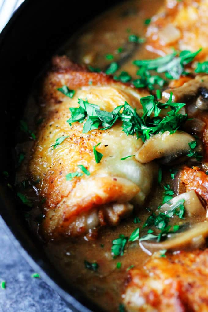 Close up of French chicken chasseur in a skillet with parsley