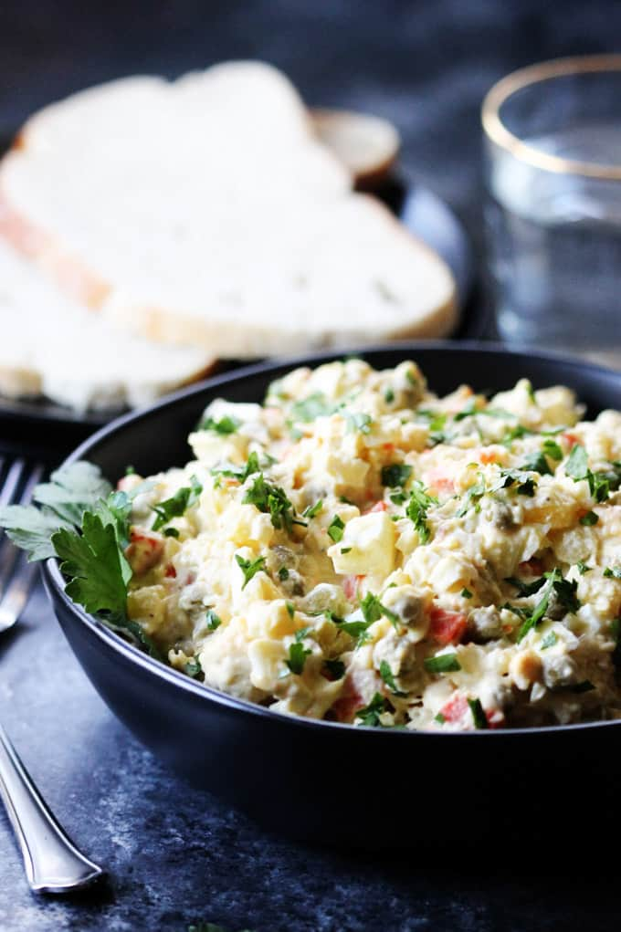 Olivier Salad in a black bowl with bread and water on a side