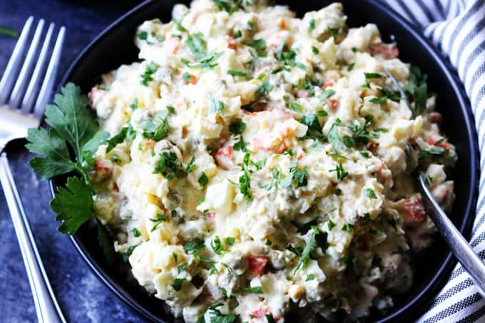 Russian potato salad in a bowl with spoon and forks on a side