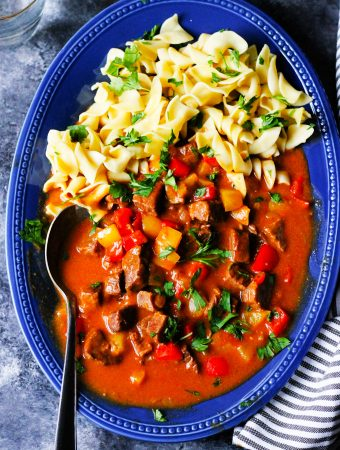 Hungarian Goulash on a blue plate with noodles and spoon