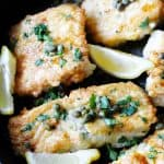 Pan fried fish with butter lemon sauce in a skillet