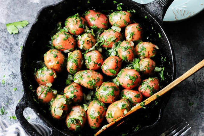Overhead shot of parsley potatoes in a skillet with wooden spoon