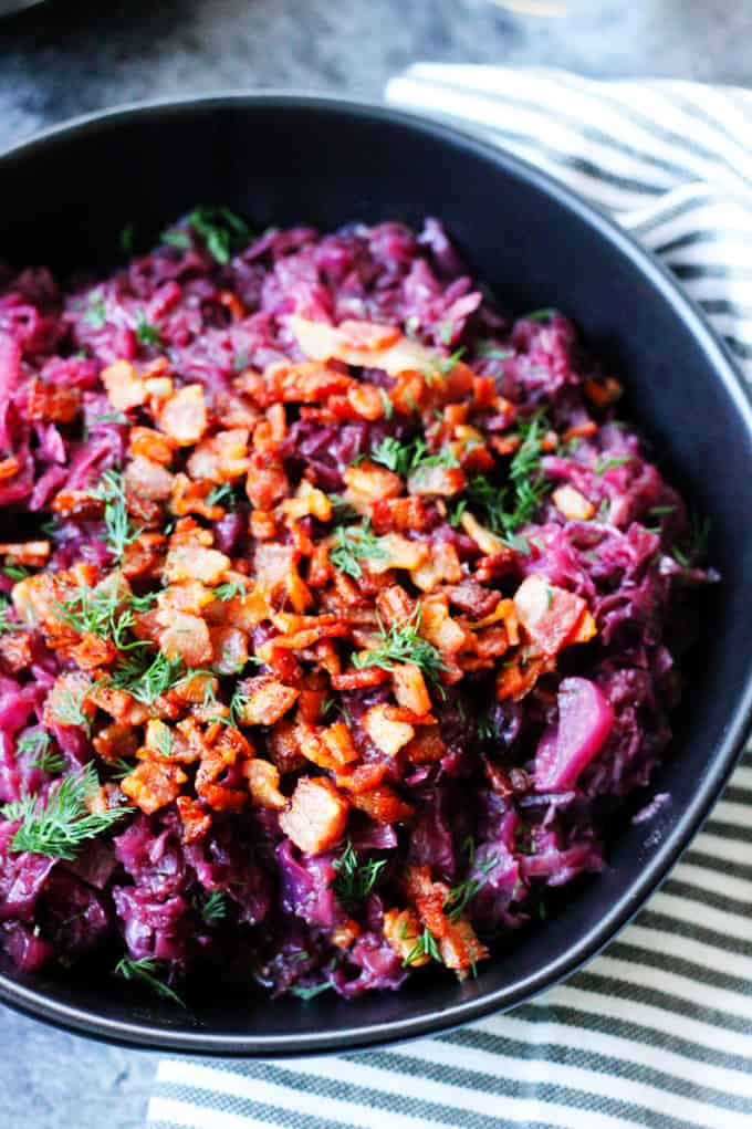 Rotkohl - German Braised Red Cabbage in a black bowl with bacon bits on top