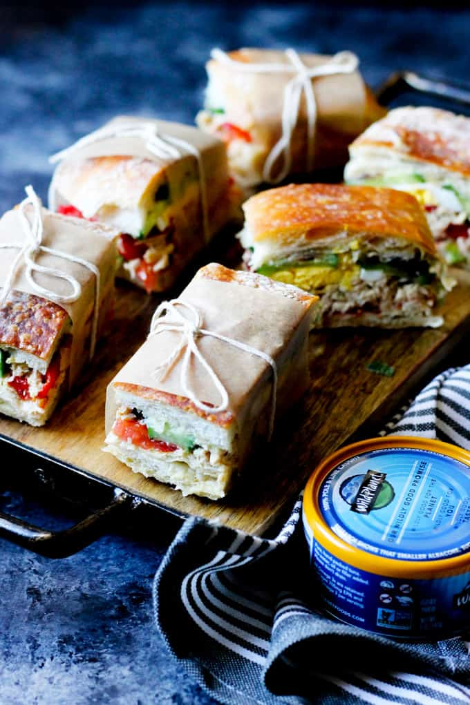Pan bagnat sandwiches on a serving board with canned tuna next to it