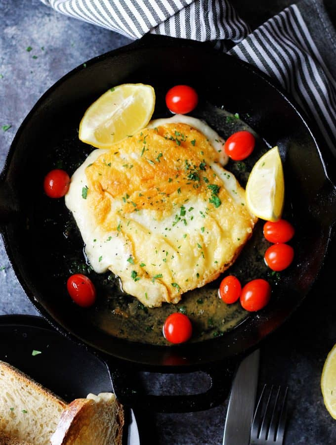 Saganaki - Greek Fried Cheese in a skillet with lemons and cherry tomatoes