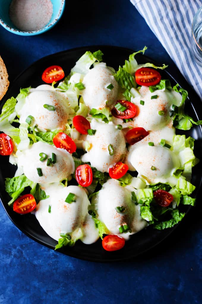Eggs Mayonnaise on a serving plate garnished with tomatoes and green onions