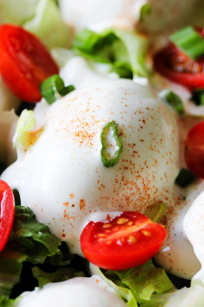 Close up photo of Eggs Mayonnaise with cherry tomatoes and scallions