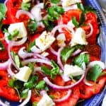Tomato Feta Salad with herbs on a blue serving plate