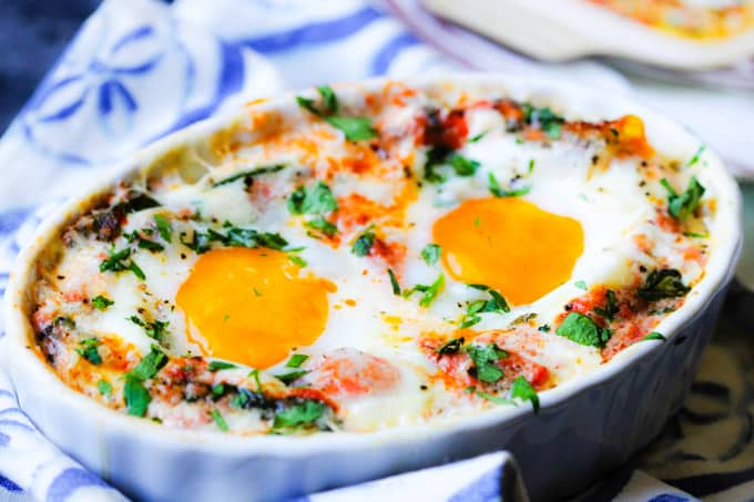 Baked eggs in white ramekin with creamy tomato spinach sauce