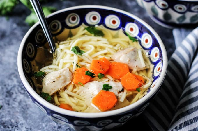 Horizontal photo of a Polish Chicken Soup in a bowl with spoon