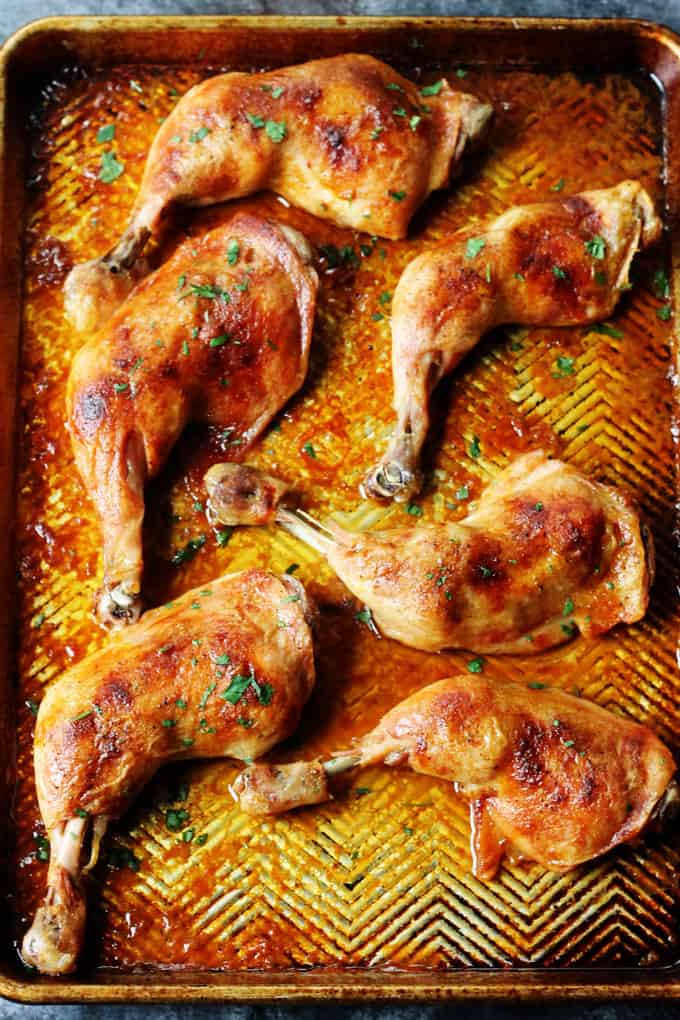Slow roasted chicken leg quarters on a sheet pan