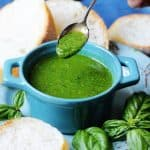 Basil sauce in a blue ramekin with spoon