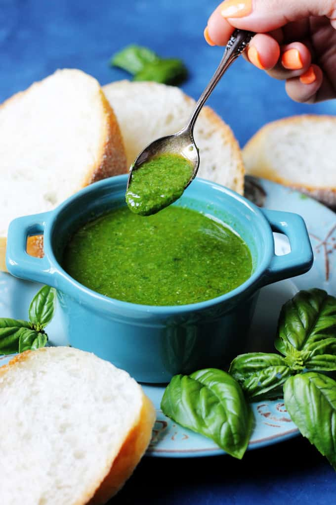Basil sauce in a blue ramekin with spoon