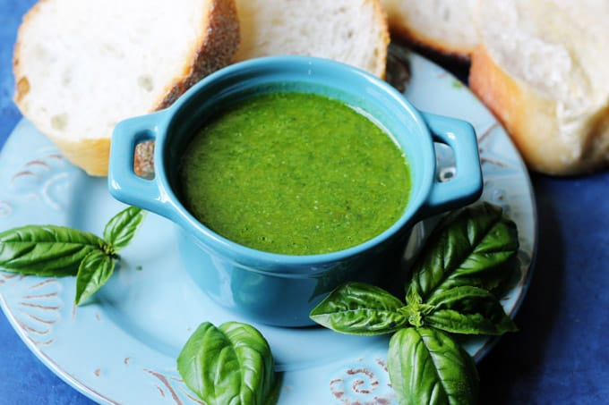 Horizontal shot of basil sauce in blue ramekin and bread on a side