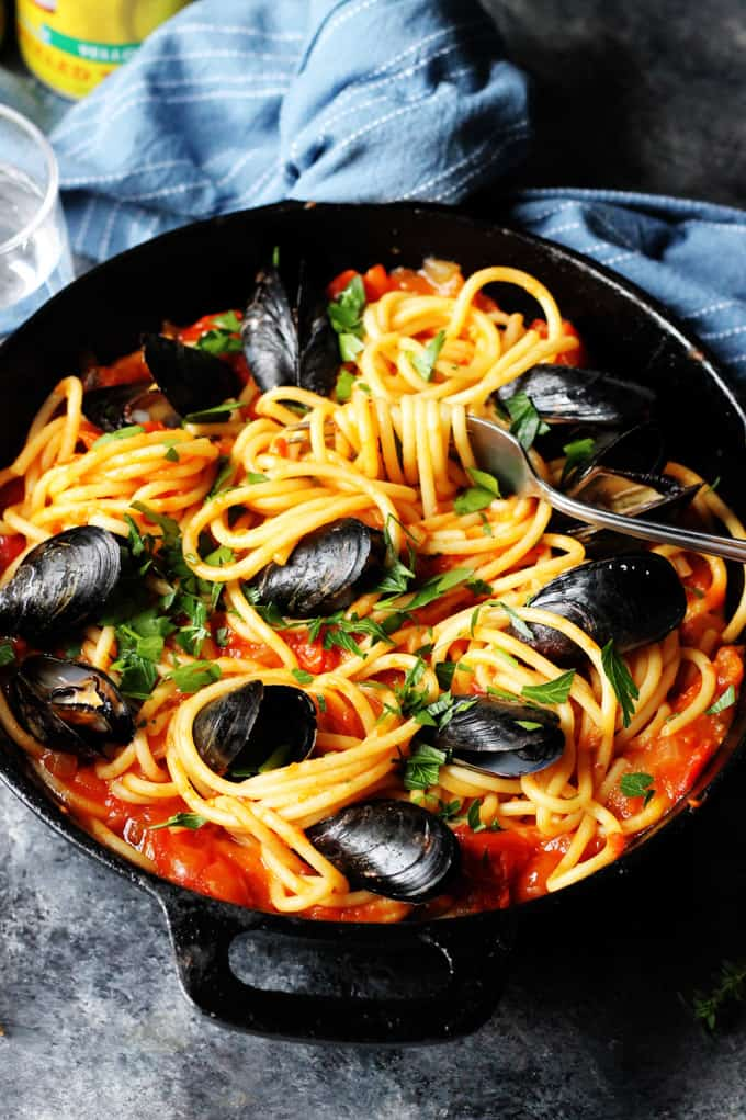 Pasta with Mussels and tomato sauce in a black skillet