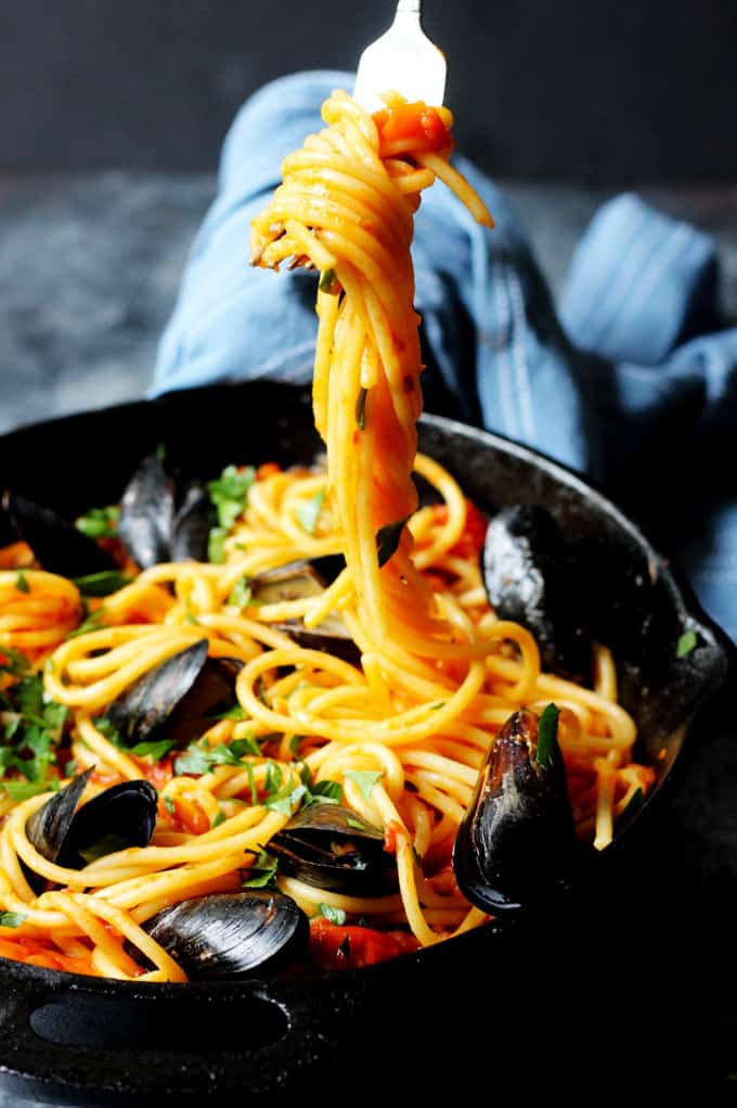Fork picking up pasta from a skillet with bucatini and mussels